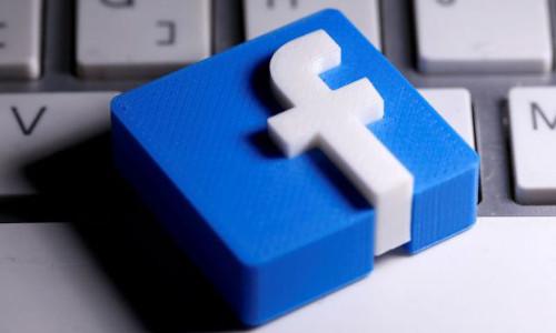 A 3D-printed Facebook logo on a keyboard.